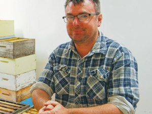 Waiau Apiaries' Nick Belton with honey frames being held in a warming room before going to the centrifugal extractors.