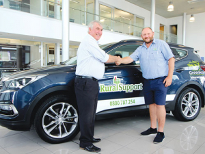 Greenlea livestock manager Bruce Mudgway (right) hands over a Santa Fe to WRST chair Neil Bateup.