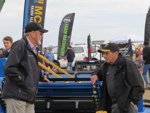 Founding director Bill McIntosh (right) at McIntosh Farm Machinery's Fieldays site solving the world's problems with Brian Hight.