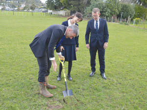 National's primary industries spokesman Nathan Guy turns the first soil at Mt Albert Grammar School, watched by agribusiness student Fatima Imraan (17) and principal Patrick Drumm.